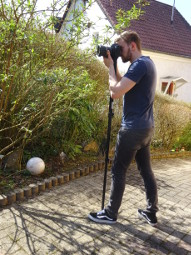 Mann steht mit Einbeinstativ auf einem Weg und schaut dank seines Einbeinstativs in die Kamera, die sich darauf befindet.