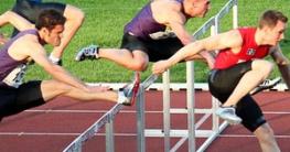 Mehrere Sportler springen über Hürden in einen Station. Die Aufnahme entstand durch ein flexibles Einbeinstativ
