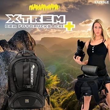 Kamerarucksack von Xtrem. Frau hält Kamera, die sie aus der Tasche gezogen hat. Im Hintergrund geht die Sonne bei einer schönen Landschaft unter.